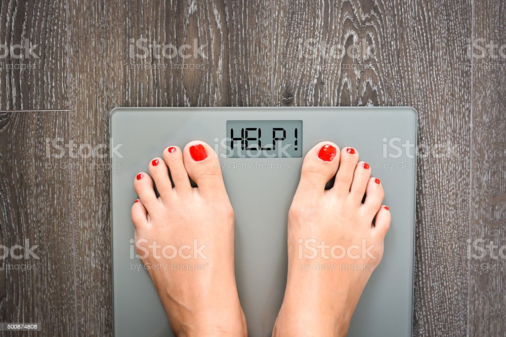 Bajar de peso concepto con persona en una escala de medición kilogramos - foto de stock