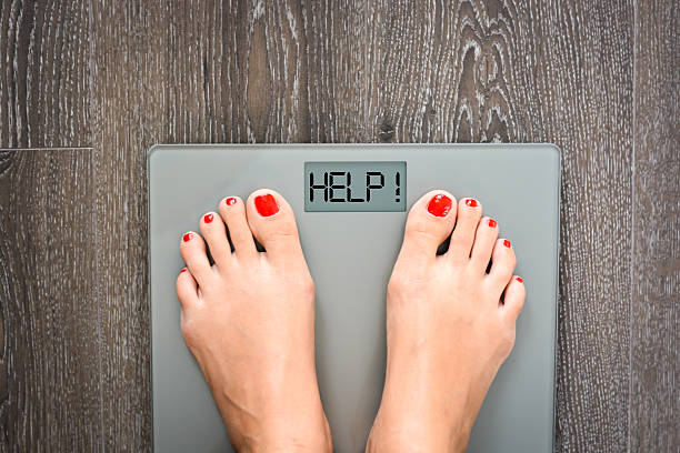 Lose weight concept with person on a scale measuring kilograms stock photo