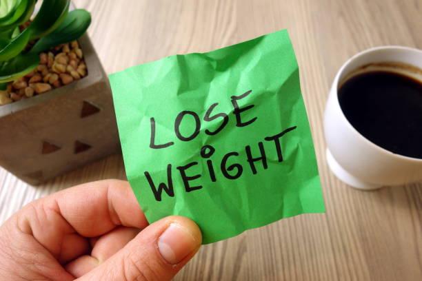 Lose weight - motivational reminder handwritten on sticky note stock photo