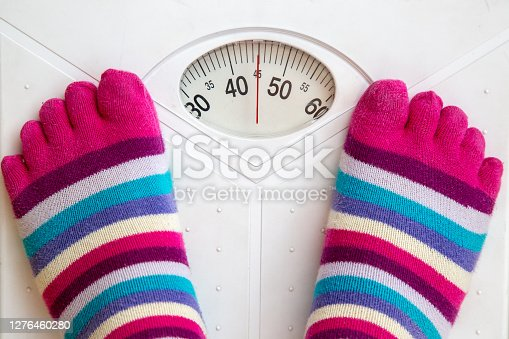 Female standing on the weight scale with funny socks