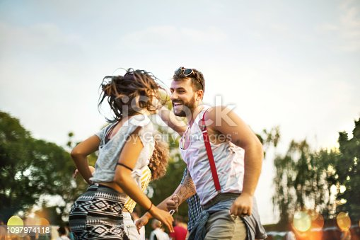 Young couple dancing at music festival.