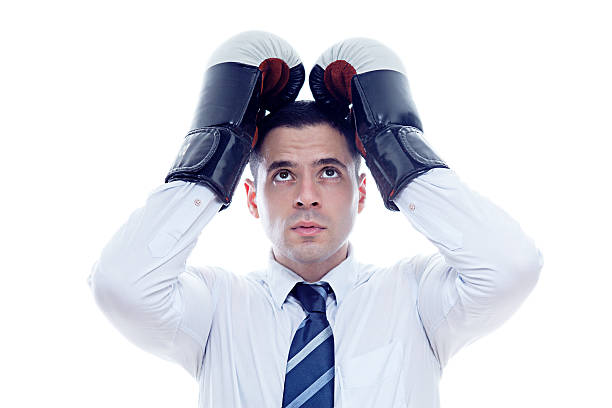 Loser businessman covers his head with boxing gloves stock photo