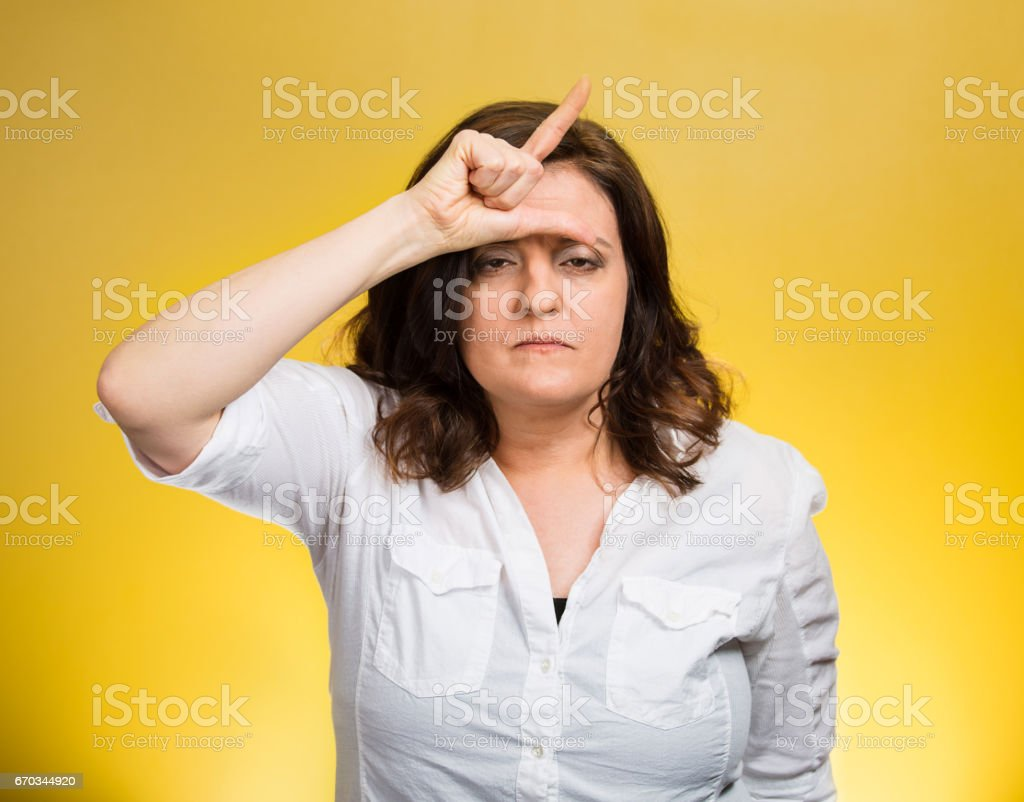 Loser. Closeup portrait funny mature middle aged woman giving loser sign on forehead stock photo