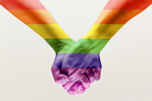 Ð¡loseup of a gay couple holding hands, patterned as the rainbow flag Right to choose your own way. Ð¡loseup shot of a gay couple holding hands, patterned as the rainbow flag isolated on white studio background. Concept of LGBT, activism, community and freedom. month stock pictures, royalty-free photos & images