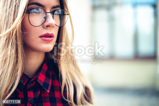 870648602 istock photo lose-up portrait of inspired young woman Lady wearing eyeglasses, wrist watch. Female fashion concept 905771128