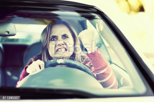 1138361116 istock photo Losing her temper, a woman driver shakes fist through windshield 511390337