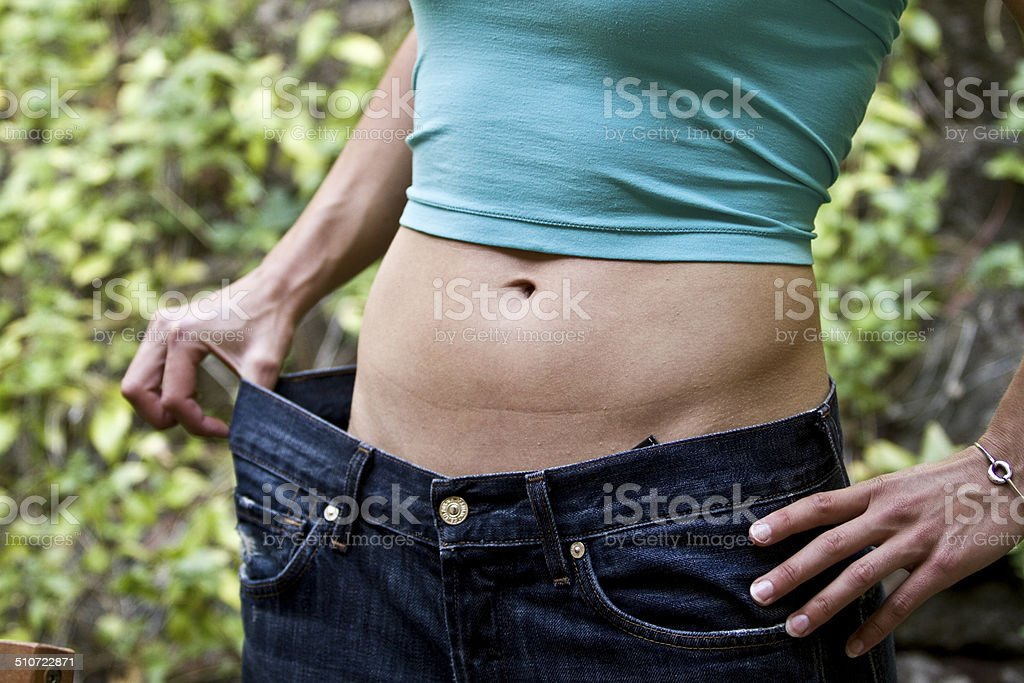 Losing weight around waist in blue jeans stock photo