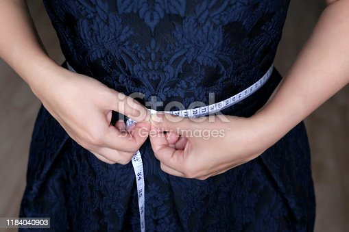 1163494373 istock photo Losing weight concept, girl in blue dress standing with measuring tape around the waist 1184040903