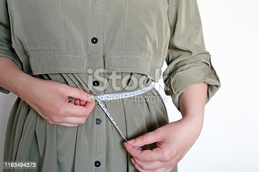1163494373 istock photo Losing weight concept, girl in dress with measuring tape around the waist 1163494373