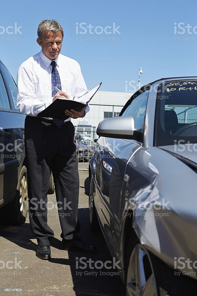 Loss adjuster inspecting damaged car stock photo