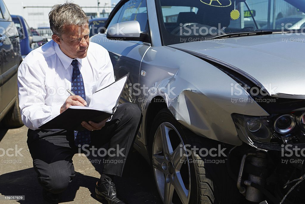 Loss adjuster inspecting wrecked car stock photo