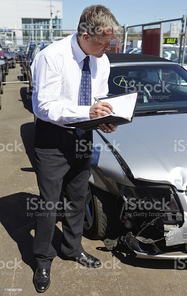 A loss adjuster looking at a car involved in an accident stock photo