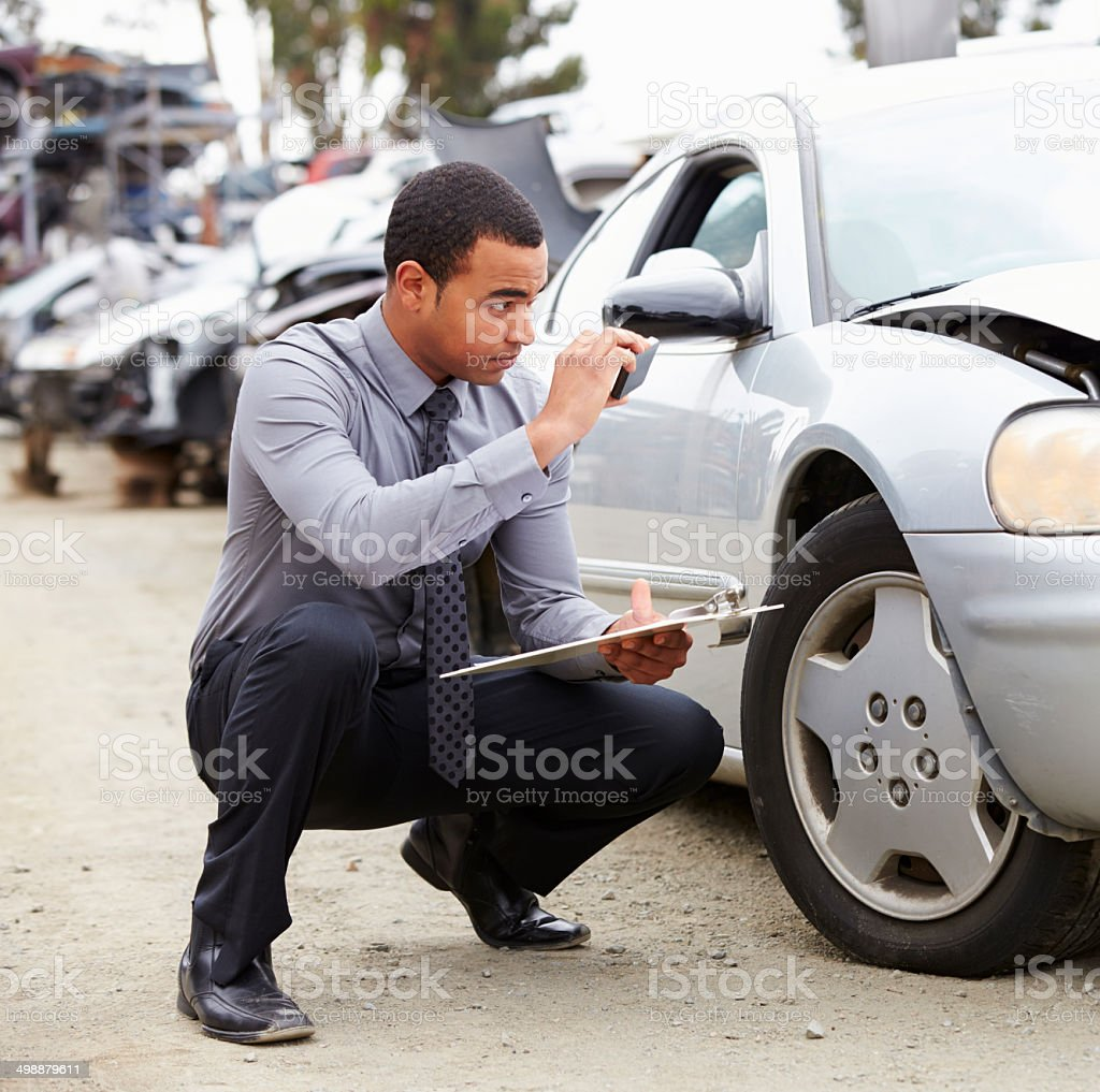 Loss Adjuster Taking Photograph Of Damage To Car stock photo