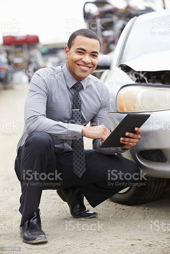 Loss Adjuster Using Digital Tablet In Car Wreck Inspection stock photo