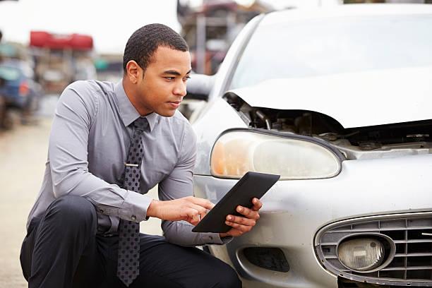 loss adjuster using digital tablet - krockad bil bildbanksfoton och bilder