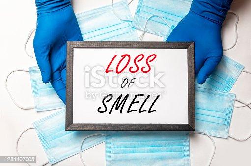 Loss of smell inscription on paper in hands in gloves. anosmia disease, symptom of coronavirus.