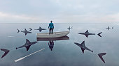 Man lost at sea in row boat made of wood. He has lost the oars and cannot sail the boat. Sharks are moving in on him. He stands up in the boat looking for a way out. Concept of failure and trying to find a solution to an emerging problem. \nNote: The man is a 3D-render. Property release attached.
