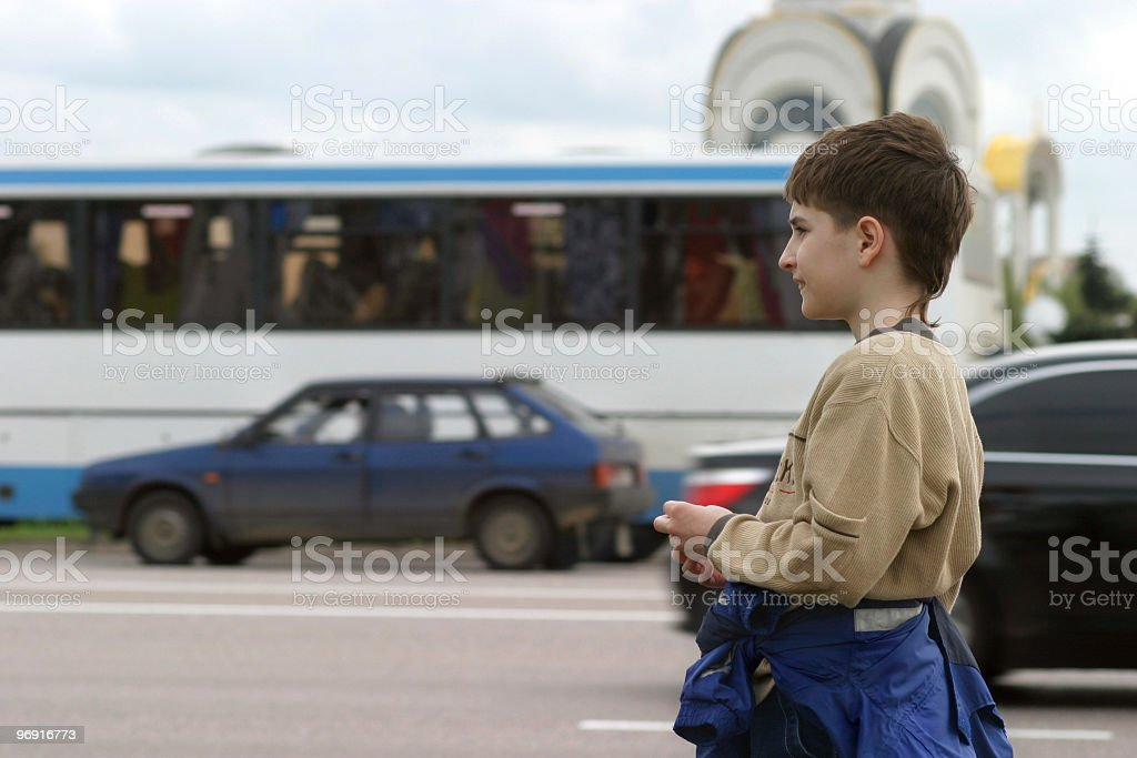 Lost boy on city street with heavy traffic royalty-free stock photo