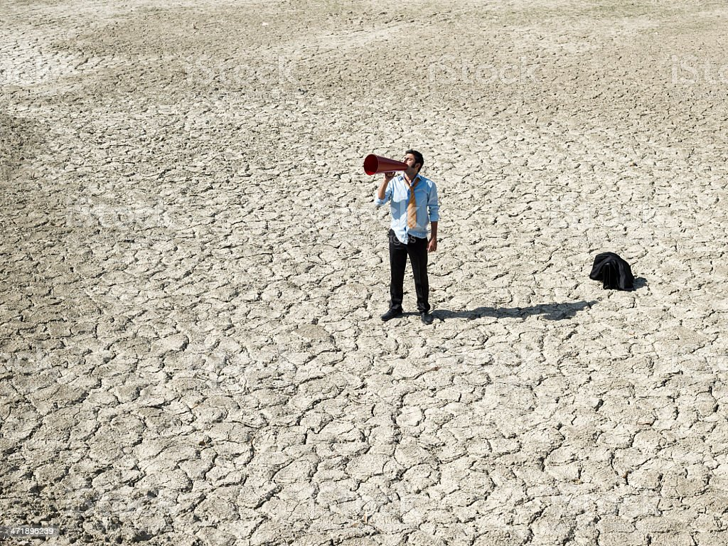 Lost businessman in desert looking for help via megaphone royalty-free stock photo