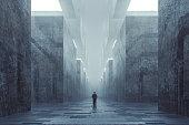 Lost businessman in futuristic dark ominous concrete city.