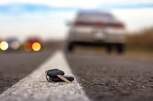 lost car keys lying on the roadway, on a blurred background with bokeh effect