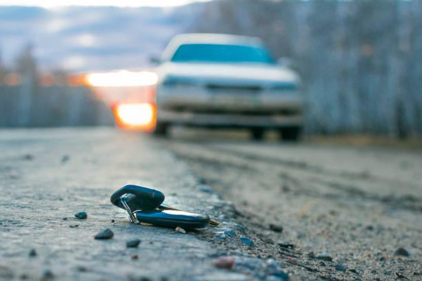 verlorene autoschlüssel auf dem asphalt, auf den unscharfen hintergrund des sportwagens - schlüssel dekorationen stock-fotos und bilder