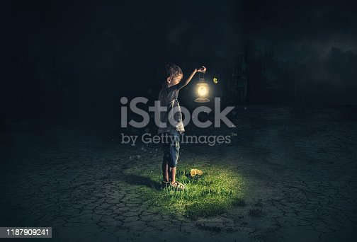 istock Lost child holding an old lamp in an apocalyptic environment 1187909241