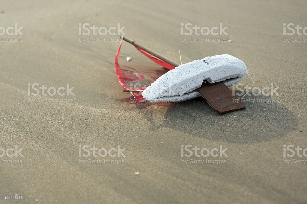 Lost child's toy boat washed up on beach royalty-free stock photo