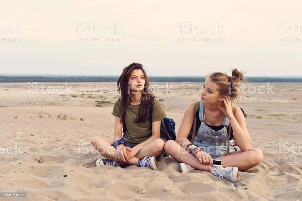 Lost female friends sitting on sand in desert Bored female friends sitting on sand. Beautiful young women are lost in desert during hiking. They are wearing casuals. 20-24 Years Stock Photo