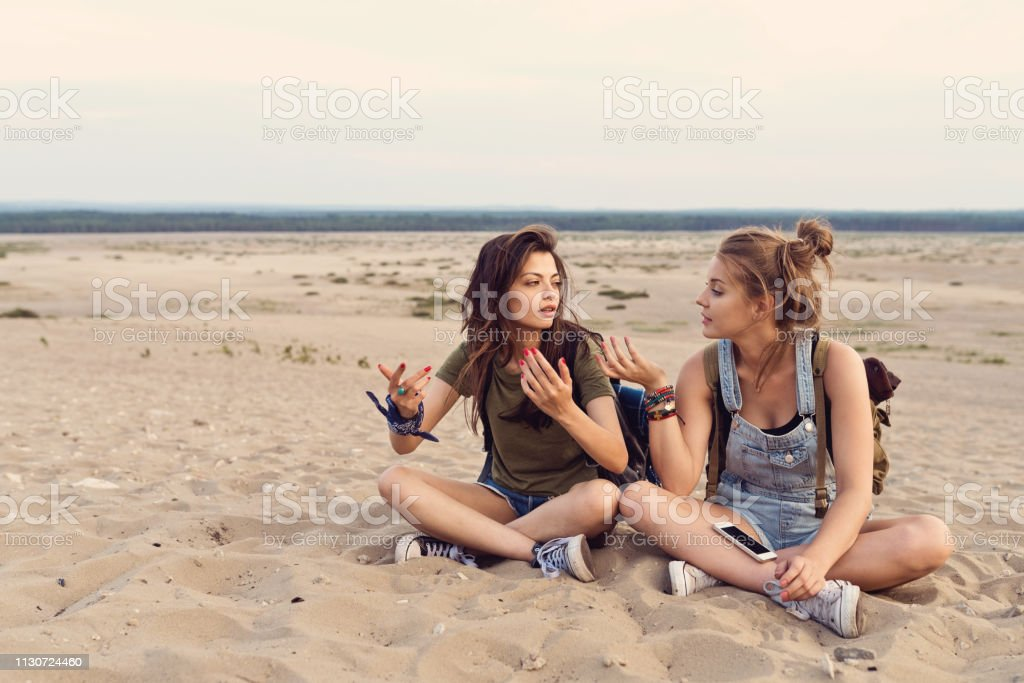Lost friends talking while sitting in desert Young women talking while sitting on sand. Female friends are lost in desert during hiking. They are wearing casuals. 20-24 Years Stock Photo