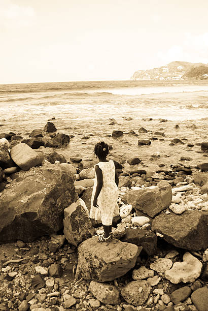 lost girl among rocks at beach stock photo