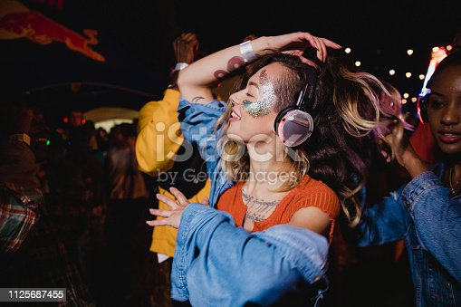 Young woman is dancing with her friends in a silent disco.