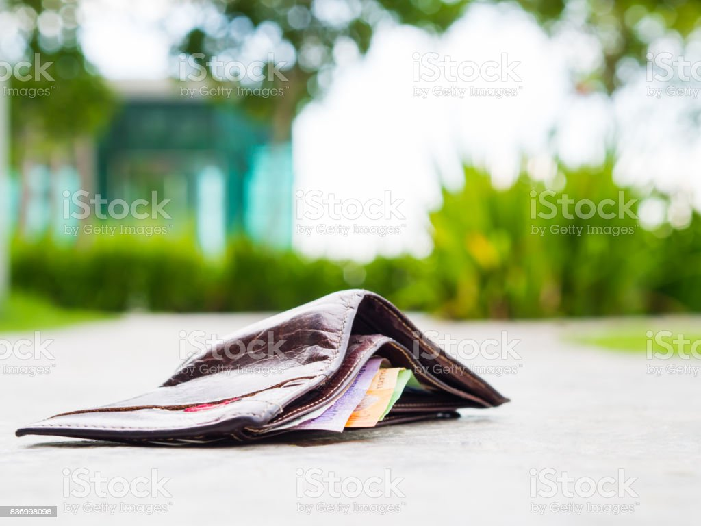 Lost leather wallet with money drop on sidewalk , lost money concept,...