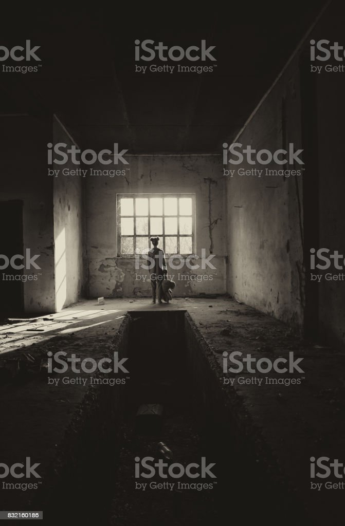 Lost little girl with teddy bear looking through window of abandoned building stock photo