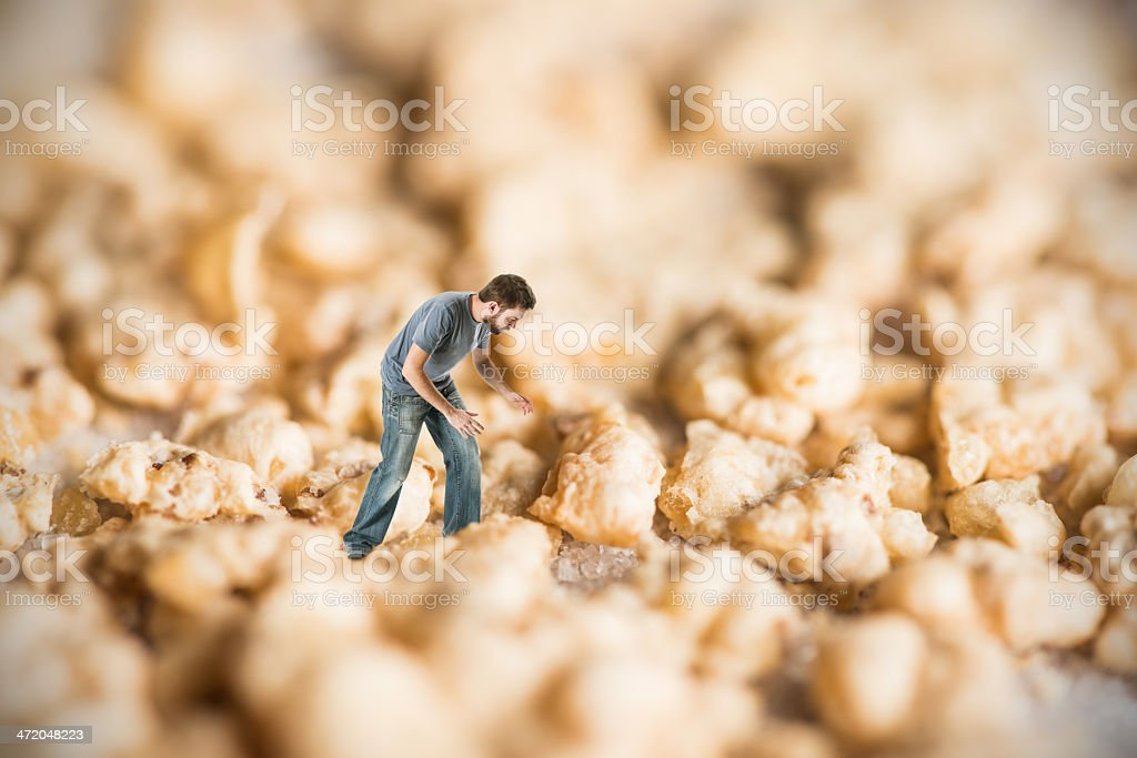 Lost man in micro world of sugar and cereal flakes royalty-free stock photo