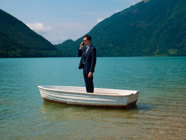 Lost Man in suit on a small boat, uses the smartphone to call. stock photo