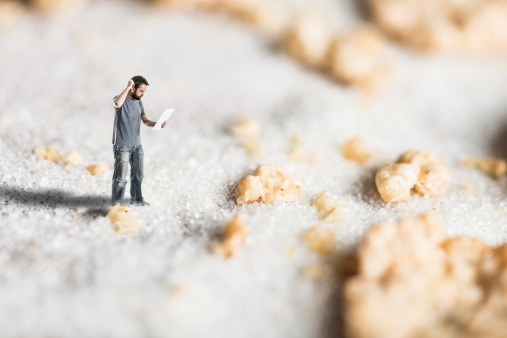 Lost man looking at map in micro world of sugar