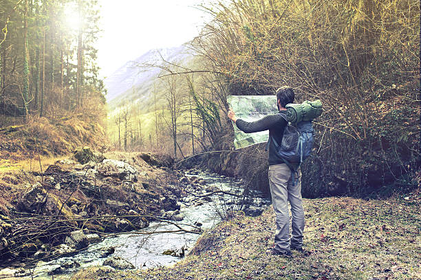 lost man observing map to find the the right way stock photo