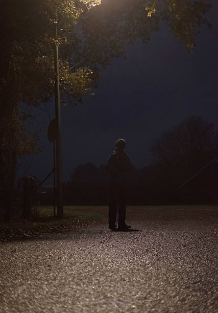 lost man standing alone on rural road at night stock photo - Spooky Halloween Pictures Free