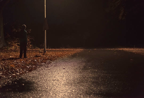 Lost man stands by side of the road at night. – Foto