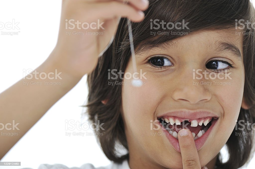 Lost milk-tooth, cute boy holding his tooth on thread stock photo