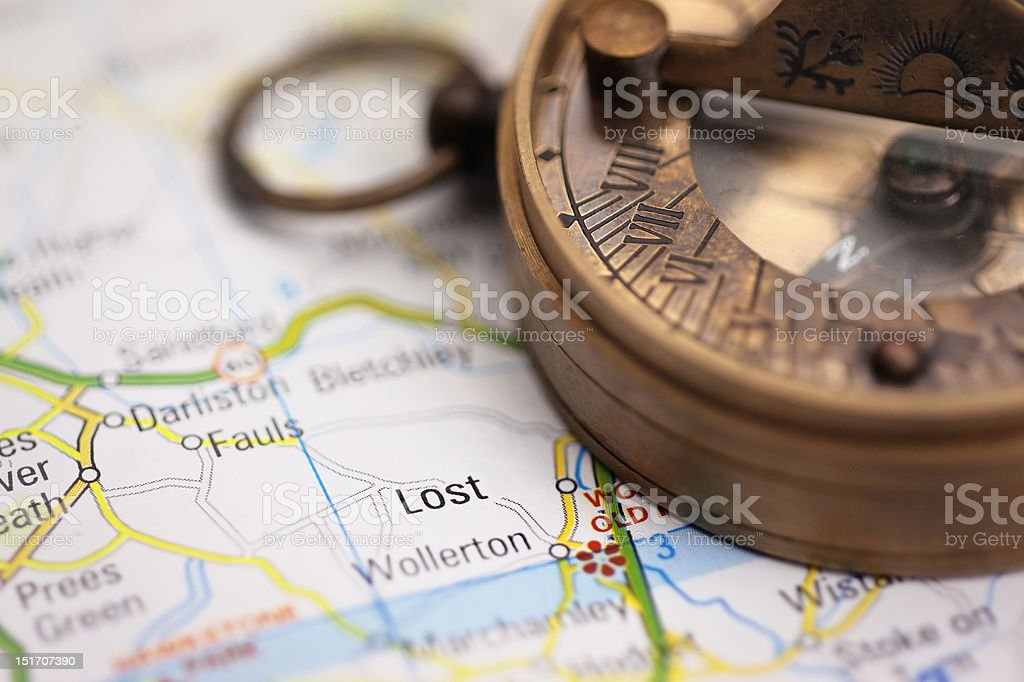 """Lost on the map - Travel concept with compass """"Lost"""" on a faked map of England, with an old-style magnetic compass. Focus on """"Lost"""" and some parts of the compass. AdobeRGB Arranging Stock Photo"""