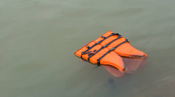 lost orange life vest floating on the river stock photo