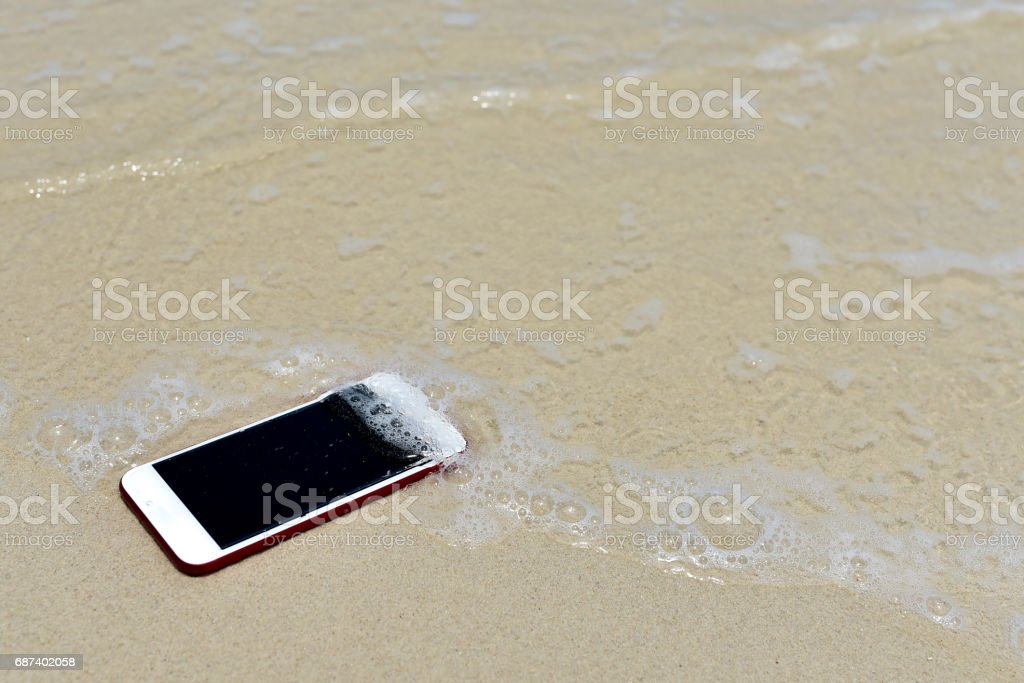 Lost Phone.Phone fell Disappear at beach for background stock photo