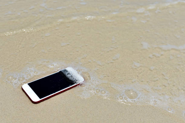 verloren phone.phone viel verdwijnen op strand voor achtergrond - cell phone toilet stockfoto's en -beelden