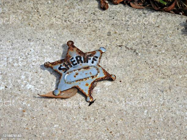 lost-rusty-sheriff-badge-on-the-pavement