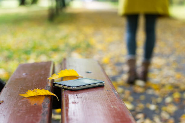 lost smart phone on a bench in public park - lost stock photos and pictures