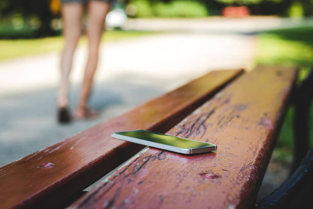 Lost smart phone on bench in public park. Woman leaving from bench where she forget her smart phone. lost stock pictures, royalty-free photos & images