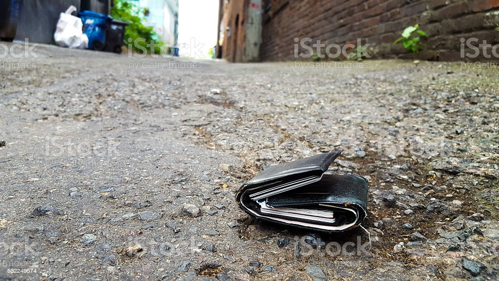 Low angle photo of a stuffed wallet lying abandoned on the ground in...