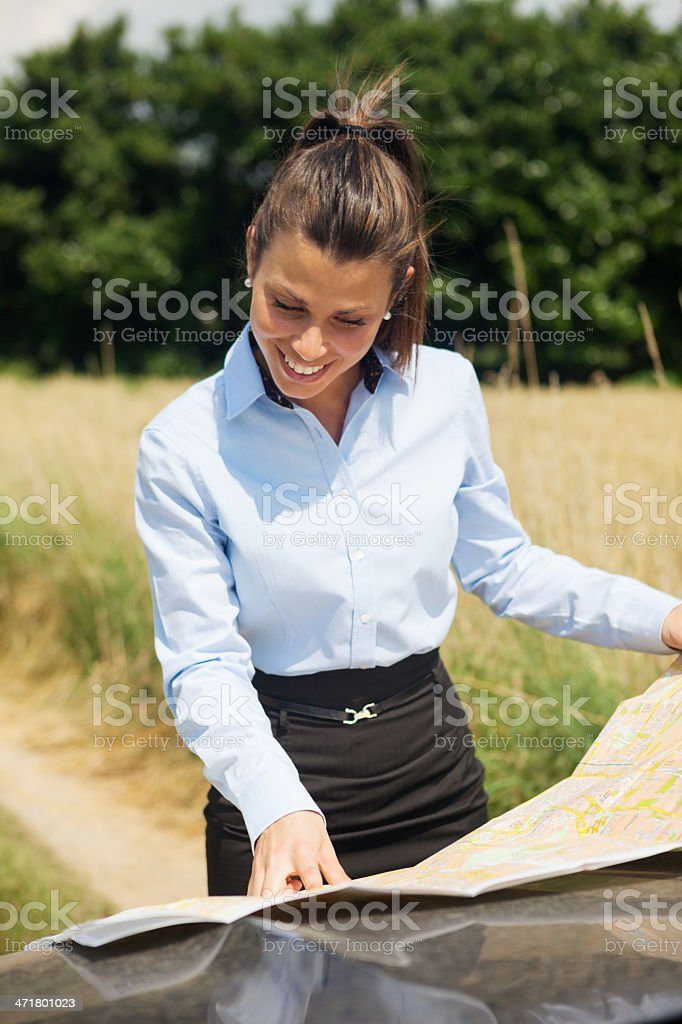 Lost woman standing outside of her car with a map royalty-free stock photo